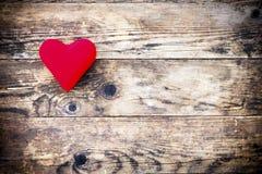 Hölzerner Hintergrund mit rotem Herzen und nichts anderes. Stockfotografie