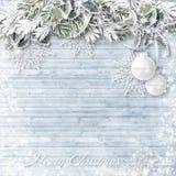 Hölzerner Hintergrund mit schneebedeckten Niederlassungen und Weihnachtsdekorationen Lizenzfreie Stockfotografie