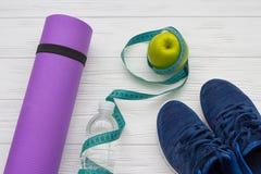 Hölzerner Hintergrund mit Schuhen, Flasche Wasser, messenden tae und Apfel Lizenzfreie Stockfotos