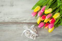 Hölzerner Hintergrund mit Tulpen und Herzen Stockfoto