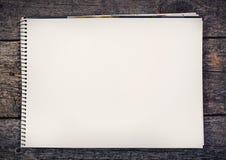 Hölzerner Hintergrund mit unbelegtem Papier Lizenzfreie Stockfotos