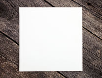 Hölzerner Hintergrund mit unbelegtem Papier Stockfotografie