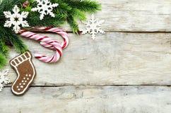 Hölzerner Hintergrund mit Weihnachtsbaum, Süßigkeit, Plätzchen und snowfla Lizenzfreie Stockfotografie