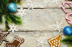 Hölzerner Hintergrund mit Weihnachtsbaum, Süßigkeit, Plätzchen und snowfla Lizenzfreie Stockbilder