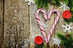 Hölzerner Hintergrund mit Weihnachtsbaum, Süßigkeit und Schneeflocken Lizenzfreies Stockfoto