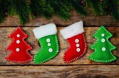 Hölzerner Hintergrund mit Weihnachtsbaum und selbst gemachten Vliesspielwaren Lizenzfreies Stockfoto