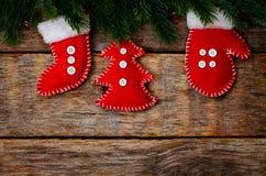Hölzerner Hintergrund mit Weihnachtsbaum und selbst gemachten Vliesspielwaren Lizenzfreie Stockfotografie
