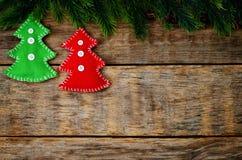 Hölzerner Hintergrund mit Weihnachtsbaum und selbst gemachten Vliesspielwaren Stockfotografie