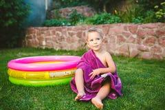 hölzerner Hintergrund und Surfbrett Ein jähriger kaukasischer Junge kleine 3, der im Hinterhof eines Hauses auf dem Gras nahe ein lizenzfreie stockfotografie