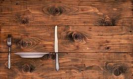 Hölzerner Hintergrund von den Brettern mit Küchengeschirr und ein Schub versehen Platte mit Rippen Lizenzfreie Stockfotografie
