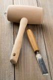 Hölzerner Holzhammer und Meißel auf Holztisch Stockfotografie