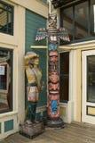 Hölzerner Inder und Totempfahl in historisch wieder hergestelltem Skagway, AK Stockbilder