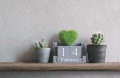 hölzerner Kalender der Weinlese für den 14. Februar mit grünem Herzen auf Holz t Lizenzfreies Stockbild