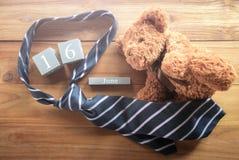 hölzerner Kalender der Weinlese für den 16. Juni mit Teddybären und Krawatte ha Lizenzfreie Stockbilder
