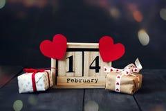 Hölzerner Kalender mit dem Datum des vom 14. Februar, Papierherzens und des Geschenks Auf einem dunklen hölzernen Hintergrund mit Stockbild