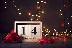 Hölzerner Kalender vom 14. Februar und eine rote Rose auf einem dunklen hölzernen Hintergrund mit Kopienraum Valentinsgruß `s Tag Lizenzfreies Stockfoto