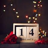 Hölzerner Kalender vom 14. Februar und eine rote Rose auf einem dunklen hölzernen Hintergrund mit Kopienraum Valentinsgruß `s Tag Stockbild