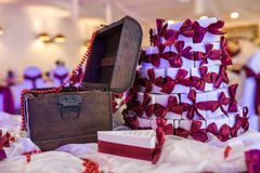 Hölzerner Kasten auf dem Tisch mit einer violetten Tischdecke und kleinen Geschenken für Gäste von den Jungvermählten stockfotografie