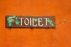 Hölzerner Kennsatz der Toilette auf der orange Wand. Lizenzfreie Stockfotografie
