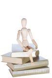 Hölzerner kleiner Mann sitzt auf Büchern Stockfoto