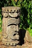 Hölzerner Kopf oder Totem des dekorativen amerikanischen Ureinwohners, propably aztekisch oder Maya, angezeigt auf Steinsockel stockfoto