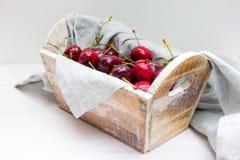 Hölzerner Korb von frischen Kirschen in einer grauen Baumwollserviette am weißen Hintergrund stockfotos