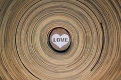 Hölzerner Kreis mit einem gemalten Herzen und das Wort lieben auf einer hölzernen Diskette des gestreiften Hintergrundes Hintergr Lizenzfreies Stockfoto