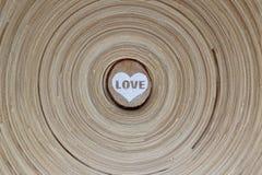 Hölzerner Kreis mit einem gemalten Herzen und das Wort lieben auf einer hölzernen Diskette des gestreiften Hintergrundes Hintergr Stockbilder