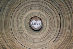 Hölzerner Kreis mit einem gemalten Herzen und das Wort lieben auf einer hölzernen Diskette des gestreiften Hintergrundes Hintergr Lizenzfreie Stockfotos