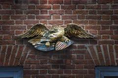Hölzerner Krieg Eagle auf warmer Backsteinmauer lizenzfreie stockfotografie