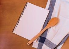 Hölzerner Löffel der Küche mit leerem Notizbuch Lizenzfreie Stockfotos