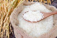 Hölzerner Löffel mit rohem Reis in der Juteleinwandtasche lizenzfreie stockbilder