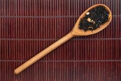 Hölzerner Löffel mit schwarzem Tee Stockbild