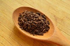 Hölzerner Löffel und harmal Samen, uzerlik heraus Stockfotografie