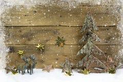Hölzerner Landhausstilweihnachtshintergrund mit Ren und Schnee Stockbilder