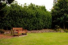 Hölzerner Lehnsessel im Garten Stockfotos