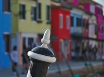 Hölzerner Liegeplatzpfosten vor bunten Häusern in Burano, Italien Stockfotografie