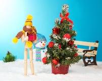 Hölzerner Mann, der ein Weihnachtsgeschenk hält Stockfoto