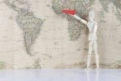 Hölzerner Mann, der Flugzeug auf Weltkarte hält Lizenzfreie Stockbilder