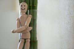 Hölzerner Mann, der zu Hause steht und auf Baum sich lehnt Lizenzfreie Stockfotos