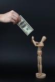 Hölzerner Mann fordert Geld an Stockfotografie