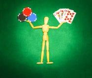 Hölzerner Mann mit den Händen bis zu den Griffchips und den Karten für das Spielen des Pokers Stockbilder