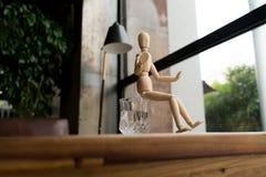 Hölzerner Mann sitzt auf einem Glas Wasser Lizenzfreie Stockfotografie