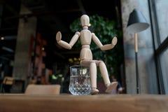Hölzerner Mann sitzt auf einem Glas Wasser Lizenzfreies Stockbild