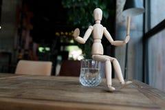 Hölzerner Mann sitzt auf einem Glas Wasser Stockbild