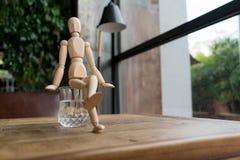 Hölzerner Mann sitzt auf einem Glas Wasser Lizenzfreie Stockfotos