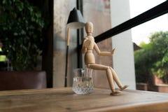Hölzerner Mann sitzt auf einem Glas Wasser Lizenzfreies Stockfoto