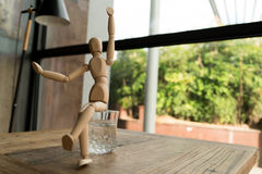 Hölzerner Mann sitzt auf einem Glas Wasser, während Erhöhung oben übergeben Stockbild