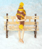 Hölzerner Mann sitzt auf einer schneebedeckten Bank Lizenzfreies Stockfoto