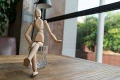 Hölzerner Mann sitzt Querbein auf einem Glas Wasser Stockbild